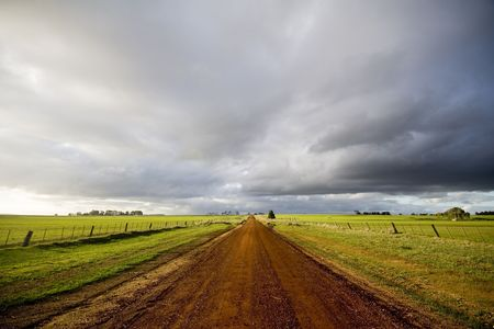 Photo for Deserted country dirt road with dark clouds and late winter light. - Royalty Free Image