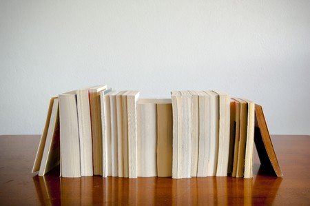 A row of books sits on a timber table with blank space behind