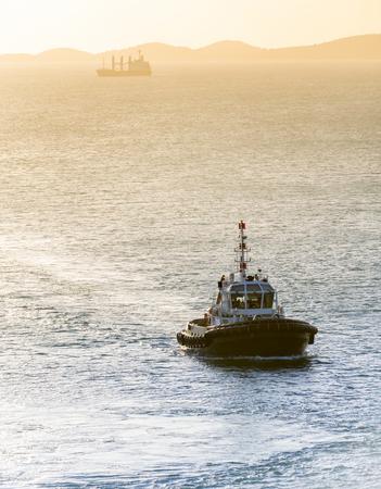 Tugboat in sunset light returning to harbor