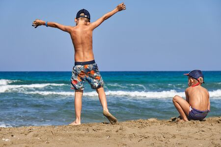 Foto de Back view of kids in shorts and caps with naked torso spending time together and having fun on seashore by water on sunny day - Imagen libre de derechos