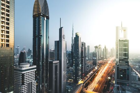 Photo pour Long exposure view of traffic and skyline from rooftop at sunset Dubai - UAE - image libre de droit