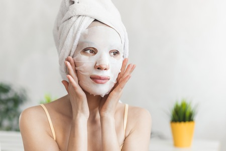 Photo for Face Skin care. Attractive Young Woman Wrapped in Bath Towel, with white moisturizing face mask - Royalty Free Image