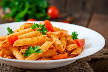 Foto de Penne pasta in tomato sauce with chicken, tomatoes on a wooden background - Imagen libre de derechos