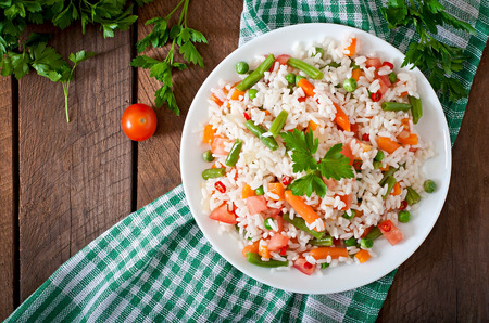 Appetizing healthy rice with vegetables in white plate on a wooden background