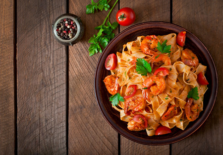 Photo pour ettuccine pasta with shrimp tomatoes and herbs - image libre de droit