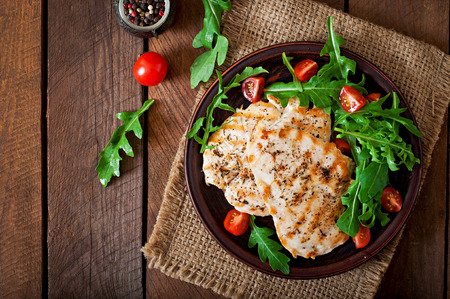 Chicken breast with fresh salad arugula and tomato