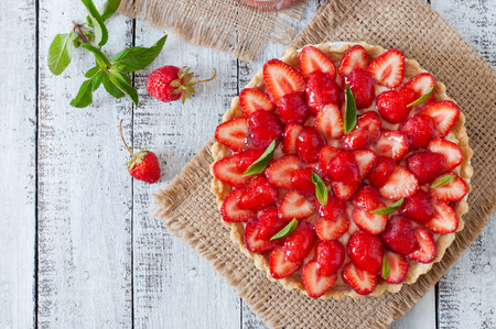 Photo pour Tart with strawberries and whipped cream decorated with mint leaves - image libre de droit