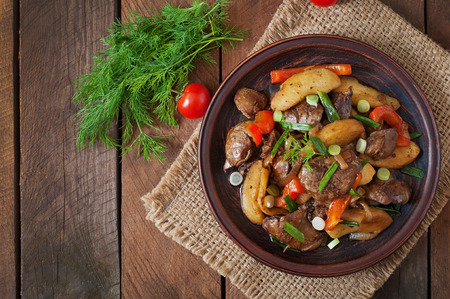 Roast chicken liver with vegetables on wooden background