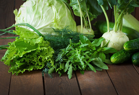 Useful green vegetables on a wooden background