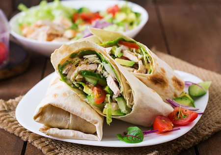 Foto de Fresh tortilla wraps with chicken and fresh vegetables on plate - Imagen libre de derechos