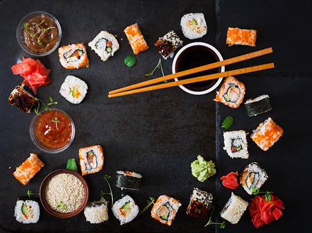 Foto de Traditional Japanese food - sushi, rolls and sauce on a dark background. Top view - Imagen libre de derechos