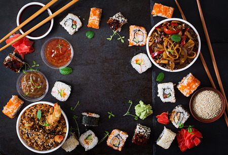 Foto de Traditional Japanese food - sushi, rolls, rice with shrimp and udon noodles with chicken and mushrooms on a dark background. Top view - Imagen libre de derechos