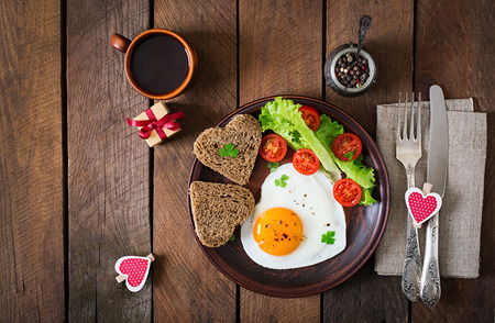 Foto de Breakfast on Valentine's Day - fried eggs and bread in the shape of a heart and fresh vegetables. Top view - Imagen libre de derechos