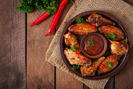 Sour-sweet baked chicken wings and sauce.Top view