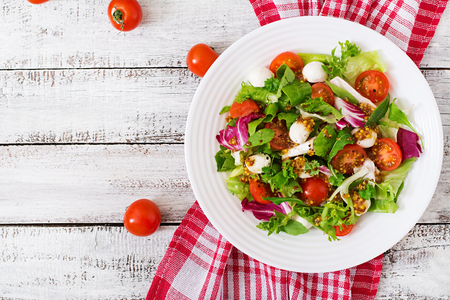 Dietary salad with tomatoes, mozzarella lettuce with honey-mustard dressing. Top view
