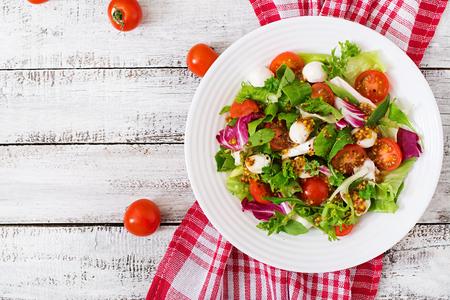 Foto de Dietary salad with tomatoes, mozzarella lettuce with honey-mustard dressing. Top view - Imagen libre de derechos
