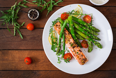 Foto de Baked salmon garnished with asparagus and tomatoes with herbs. Top view - Imagen libre de derechos