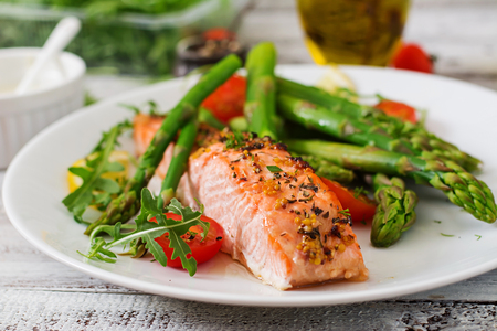 Photo pour Baked salmon garnished with asparagus and tomatoes with herbs - image libre de droit