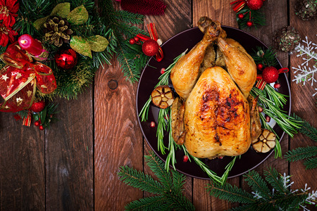 Photo pour Baked turkey or chicken. The Christmas table is served with a turkey, decorated with bright tinsel and candles. Fried chicken, table. Christmas dinner. Flat lay. Top view - image libre de droit