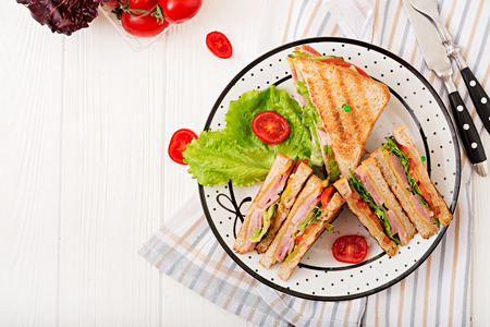Photo pour Club sandwich - panini with ham, cheese, tomato and herbs. Top view - image libre de droit