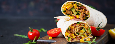Foto de Burritos wraps with beef and vegetables on  black background. Beef burrito, mexican food. - Imagen libre de derechos