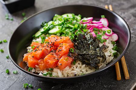 Foto de Hawaiian salmon fish poke bowl with rice, radish,cucumber, tomato, sesame seeds and seaweeds. Buddha bowl. Diet food - Imagen libre de derechos