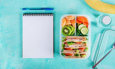 Foto de School lunch box with sandwich, vegetables, water, and fruits on table. Healthy eating habits concept. Flat lay. Top view - Imagen libre de derechos