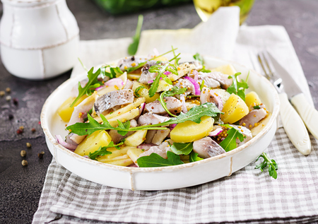 Foto de Traditional  salad of salted herring fillet, fresh apples,  red onion  and potatoes. Kosher food. Scandinavian cuisine. - Imagen libre de derechos