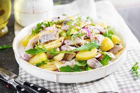Foto de Traditional  salad of salted herring fillet, fresh apples,  red onion  and potatoes. Kosher food. Scandinavian cuisine. - Imagen libre de derechos