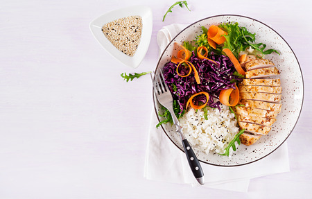 Photo pour Healthy salad. Buddha bowl dish with chicken fillet, rice,  red cabbage, carrot, fresh lettuce salad and sesame. Healthy balanced eating. Top view. - image libre de droit