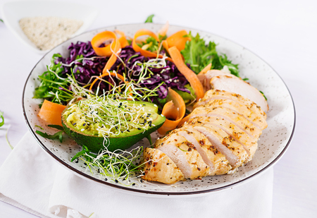 Foto de Buddha bowl dish with chicken fillet, avocado, red cabbage, carrot, fresh lettuce salad and sesame. Detox and healthy keto diet bowl concept. Overhead - Imagen libre de derechos