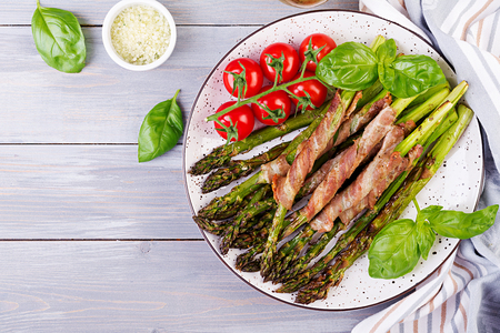 Photo for Grilled green asparagus wrapped with bacon on wooden table. Top view - Royalty Free Image