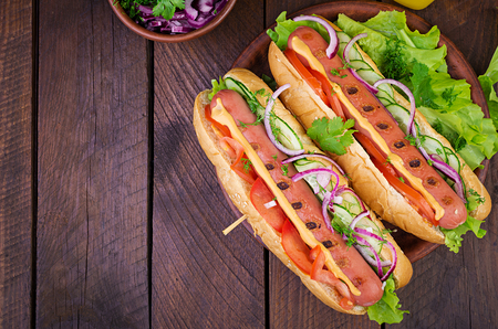 Photo for Hot dog with  sausage, cucumber, tomato and lettuce on dark wooden background. Summer hotdog. Top view - Royalty Free Image