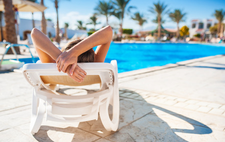 Beautiful young woman with flower in hair relaxing on sun lounger near pool.