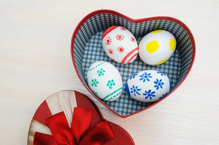 Easter colored eggs in a box in the shape of heart.