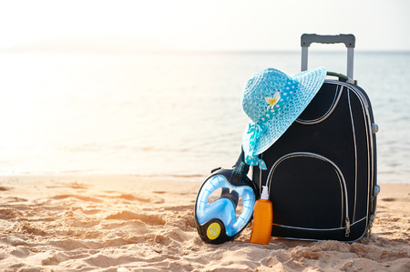 Suitcase and hat, sunscreen with a mask. The tropical sea, beach in the background. The concept of summer recreation travel and cruise traffic