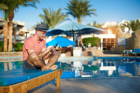 Young Man Resting On Sun Loungers By Swimming Pool and Type sms on Phone, Freelancer works remotely from the office