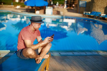 Young Man Resting On Sun Loungers By Swimming Pool and Type sms on Phone, job of a successful freelancer