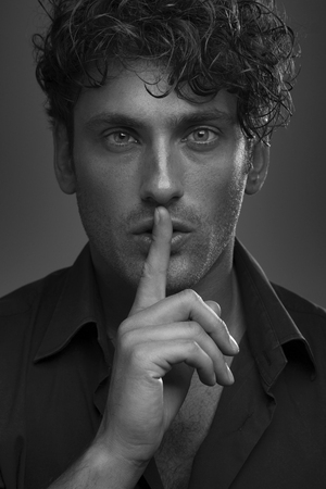 black and white portrait of serious curly man hist hush