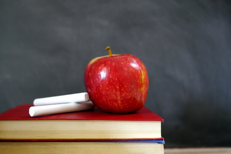 red apple and chalk on school books