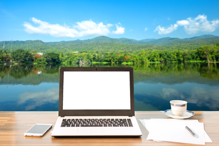 Mockup image of laptop with blank white screen,smart phone and document on wooden table of landscape forested Mountain blue sky background.