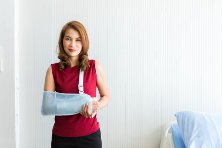 Photo pour Portrait of asian female patient in red dress broken arm after accident and wear arm splint for treatment and bed in the room hospital background,copy space - image libre de droit