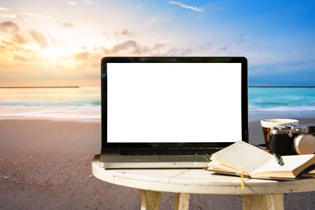 Foto de Mockup of laptop computer with empty screen with camera,notebook,coffee cup on table at landscape early sunrise over blue the sea background,working on the beach,Freelance work and holiday traveler. - Imagen libre de derechos