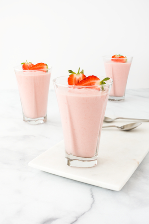 Three highball glasses filled with homemade strawberry mousse on a marble board and white marble background.