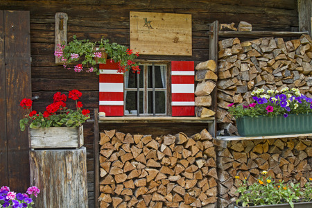 Window with shutters and flower decoration on old hut in the Karwendel mountains
