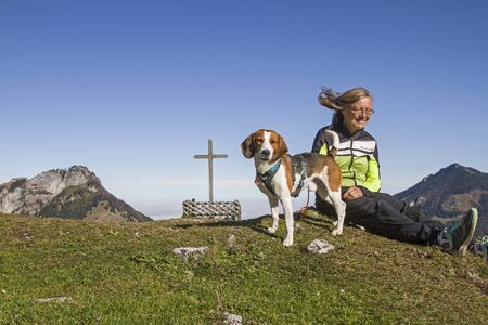 Photo for Beagle with owner defy the strong south wind, also called Föhnsturm on the Kranzhorn in the Chiemgau Alps - Royalty Free Image