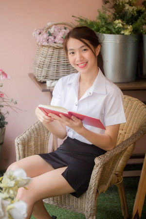 Photo for Portrait of thai adult student university uniform beautiful girl read red book - Royalty Free Image