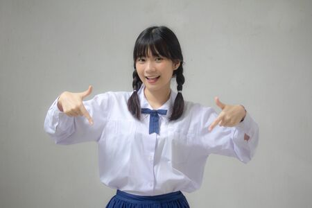 Photo pour Portrait of thai high school student uniform beautiful girl pointing - image libre de droit