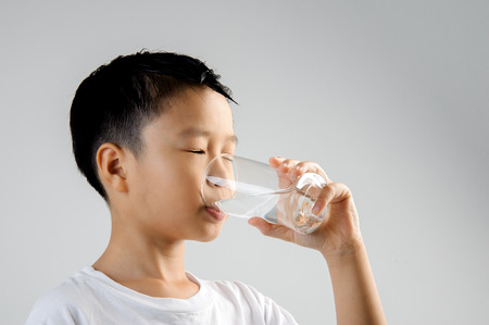 Photo for Asian young boy in white shirt hold glass of fresh water in hand and drink. Concept water day. - Royalty Free Image