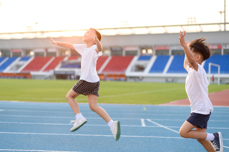 Photo pour Young Asian boy running on blue track in the stadium and happy during day time to practice himself. - image libre de droit